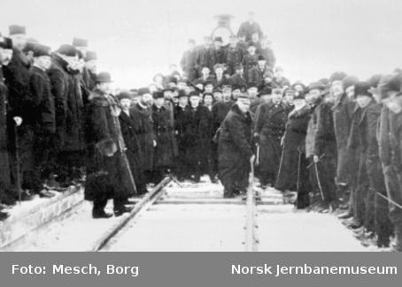 SJs generaldirektør C.F.T. Norstrøm skruer sammen skinnene ved Riksgrensen med den norske banedirektør Fleischer til høyre for ham