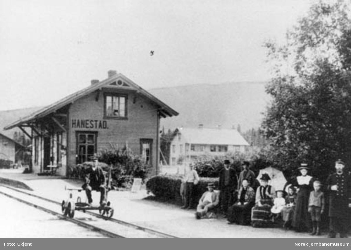 Hanestad stasjonsbygning med banevokteren på dresin og stasjonsmesteren med hans familie m.fl. i forgrunnen