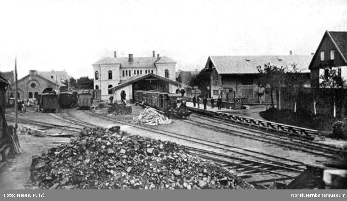 Oversiktsbilde over Trondheims første jernbanestasjon på Kalvskinnet; persontog på stasjonen
