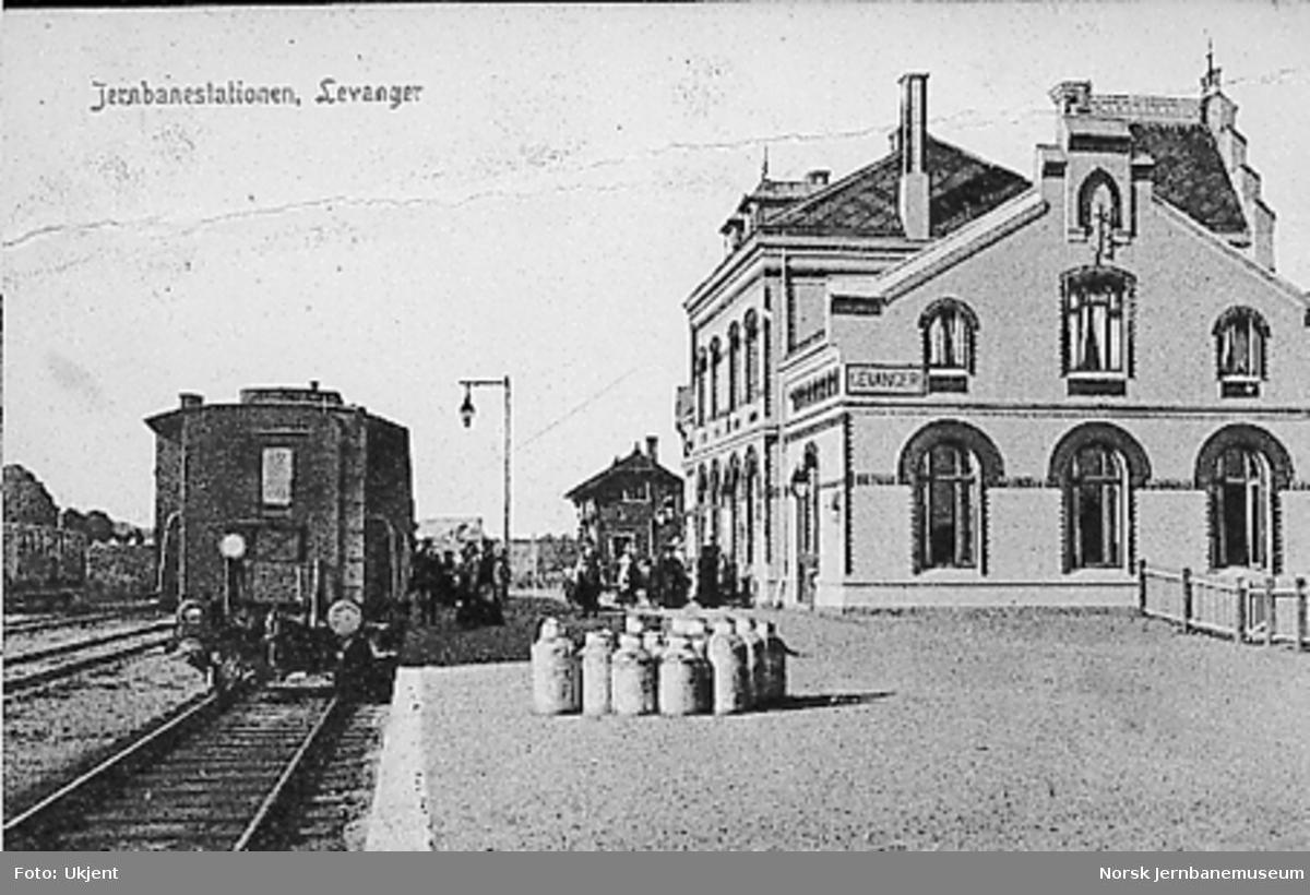 Levanger stasjon med stasjonsbygningen, reisende og tog i spor 1
