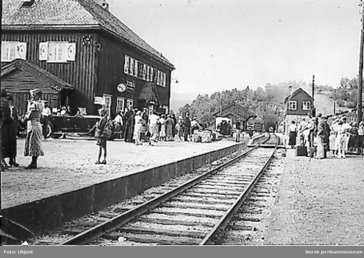 Dombås stasjon sett fra plattformen og mot tunnelen, reisende på plattformen, tog i spor 2