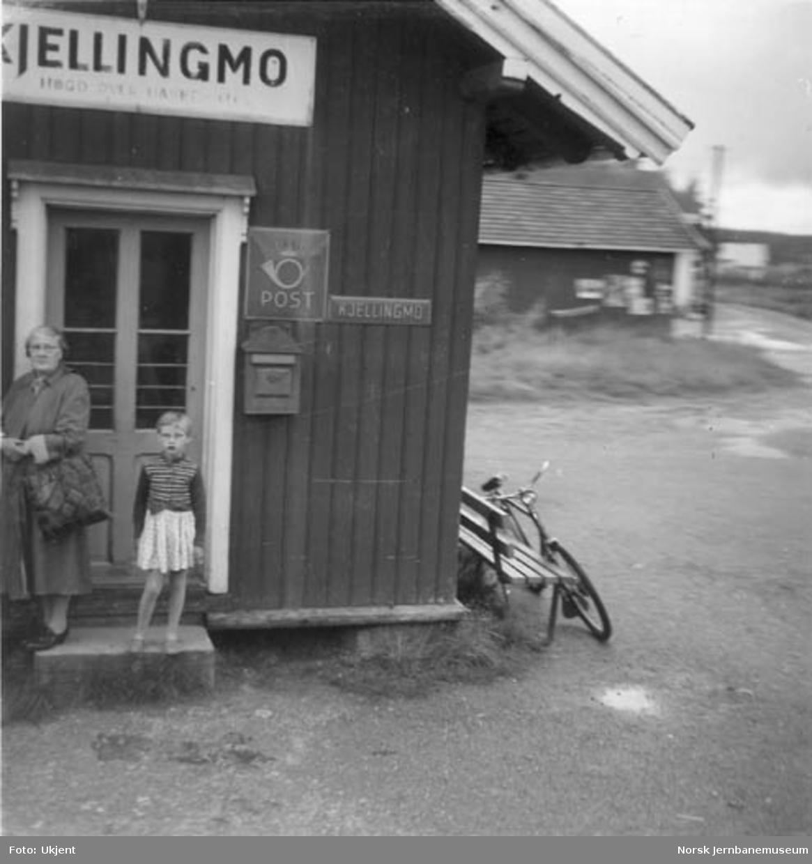 Kjellingmo stasjonsbygning, to mennesker utenfor stasjonsdøra, postskilt