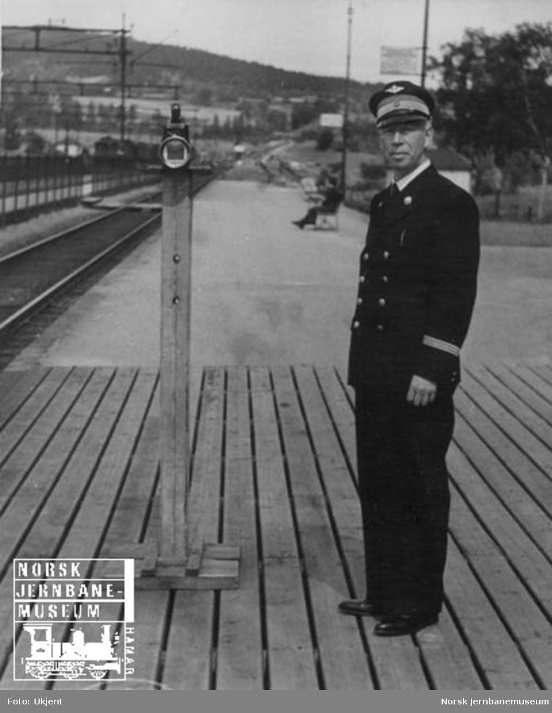 Togekspeditør gir signal til tog med lykt