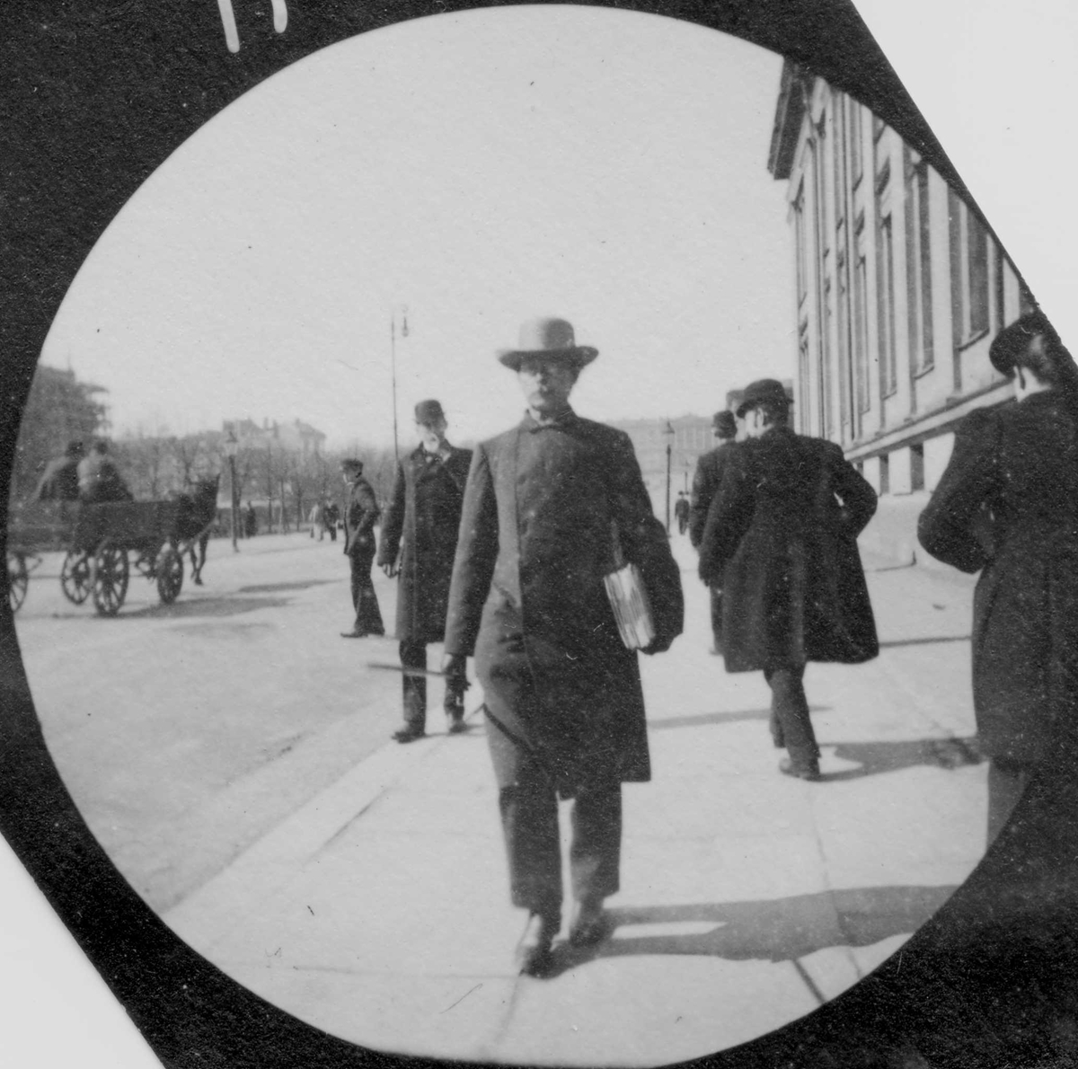 Professor G. O. Sars spaserer langs Karl Johans gate og Universitetet, Oslo. Slottet skimtes.