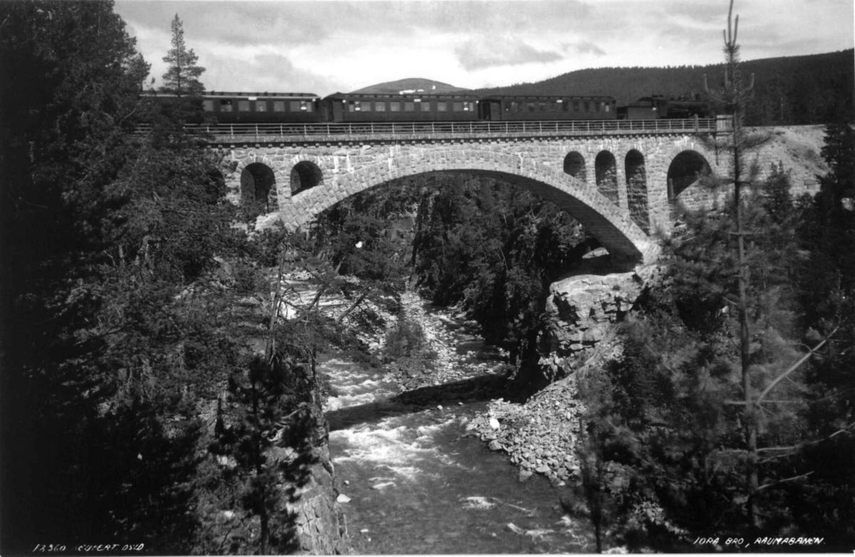 Raumabanen, Jora bro, Dombås, Dovre, Oppland 1935. Tog passerer broen. Elv. Skog.
