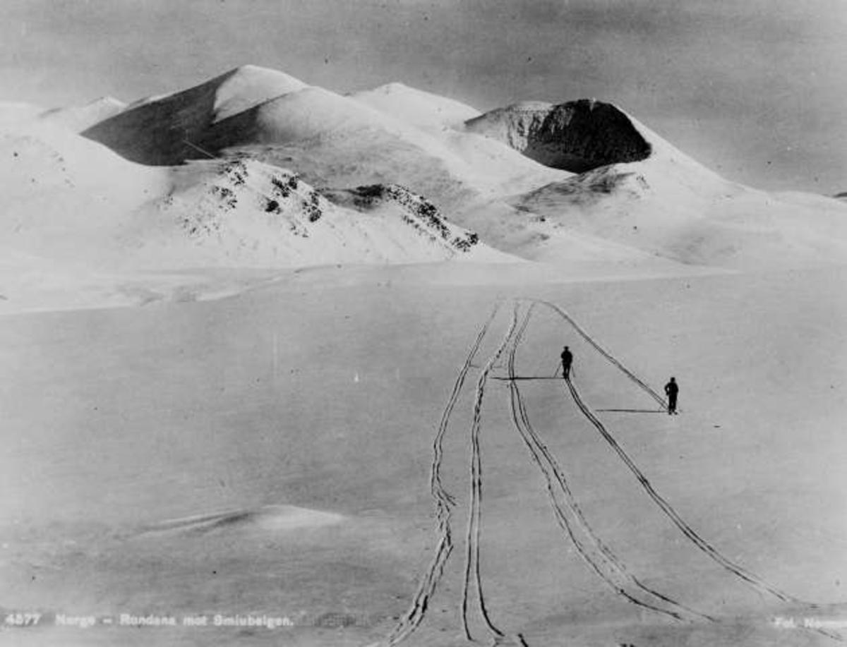 Avfotografert postkort. To skiløpere på vei hver sin vei i Rondane. Utsikt mot Smiubelgen i bakgrunnen.