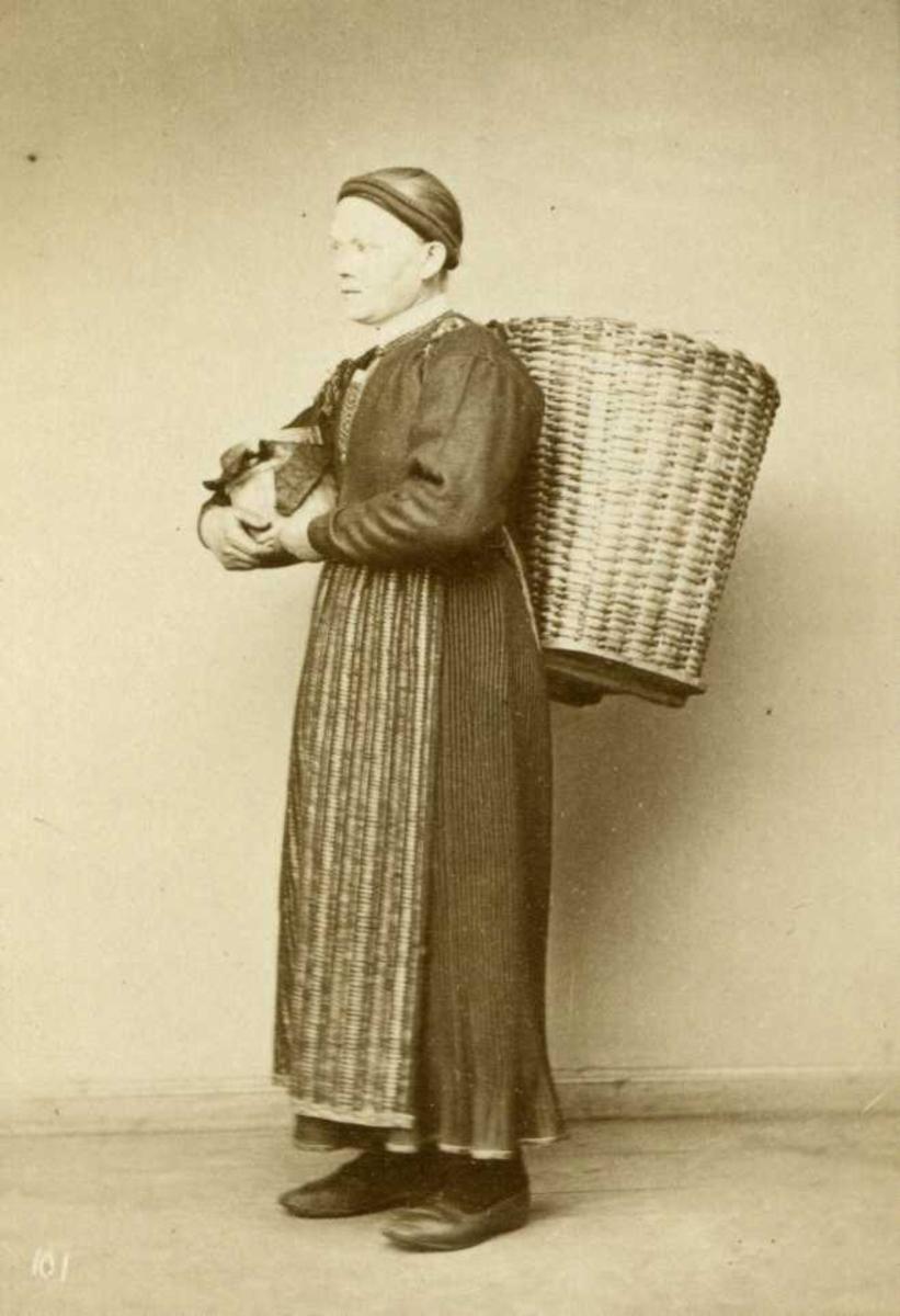 Kvinnedrakt fra Åsane, Hordaland. Visittkortformat. Kvinne med stor kurv på ryggen.