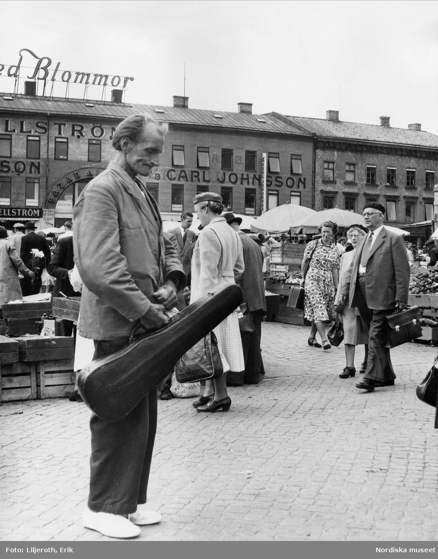 Göteborg, Kungstorget. I förgrunden en man med ett fiolfodral