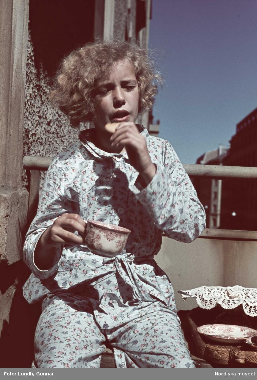 Flicka iklädd blommig pyjamas sitter på en balkong hållandes tekopp och ett kex.