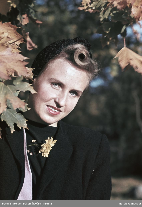 Kvinna i svart kappa, svart tröja och svart huvudbonad.