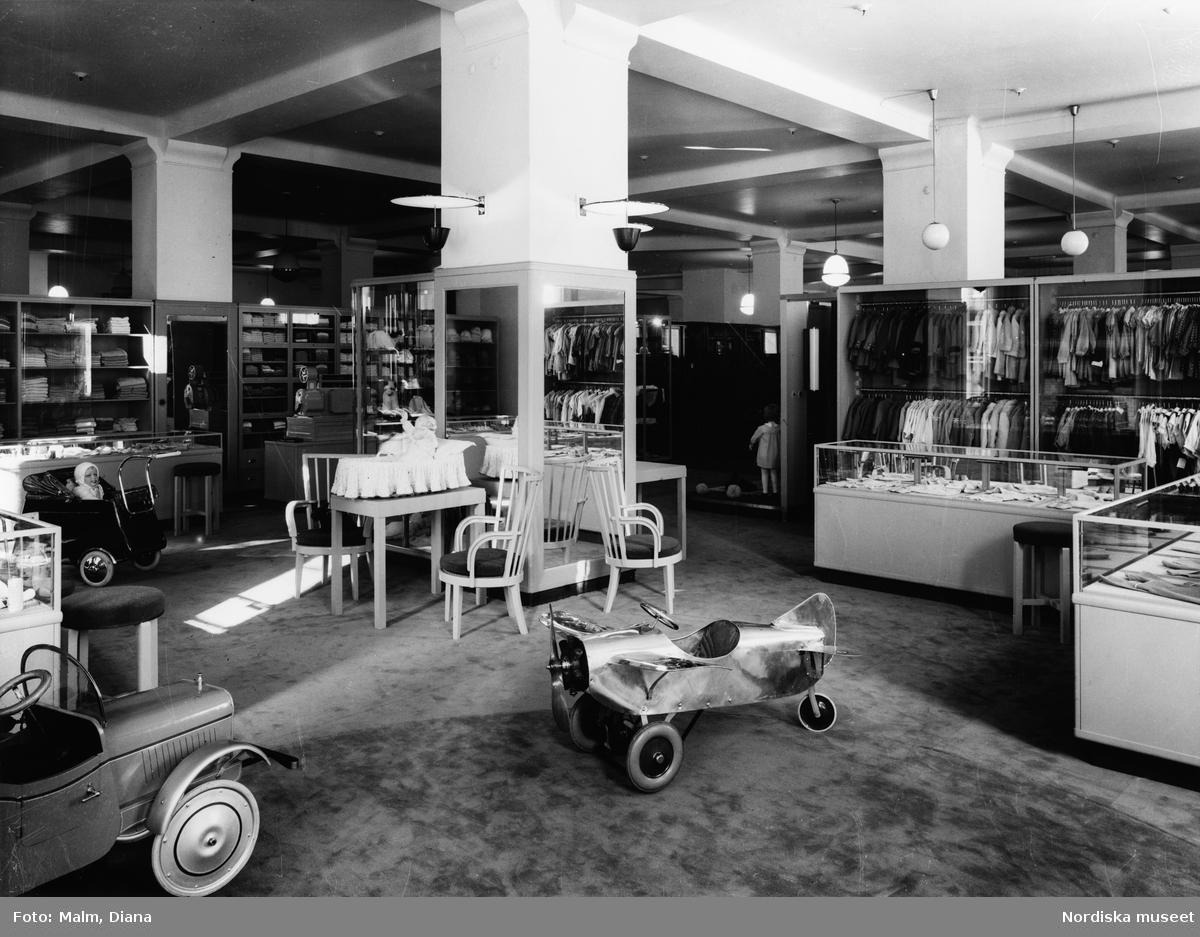 Interiör från babyavdelningen på Nordiska Kompaniet. Babykläder, dockor, barnvagn, leksaksbil och leksaksflygplan, stolar, bord och glasmontrar.