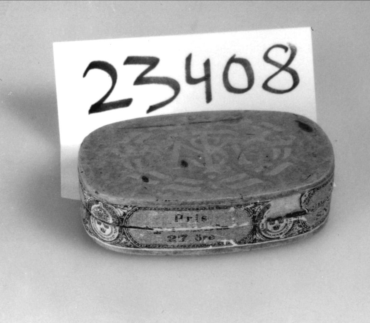 Snusförpackning av papp med pressat mönster samt initialer på ovansidan: Bokstäverna T och S skrivna på varandra i ett M (=Tobaksmonopolet). På sidorna papper med tryckt  mönster och text i grönt och vitt: N:o  901 Stockholms snus, N:o 1, Pris 27 öre samt firmamärke.