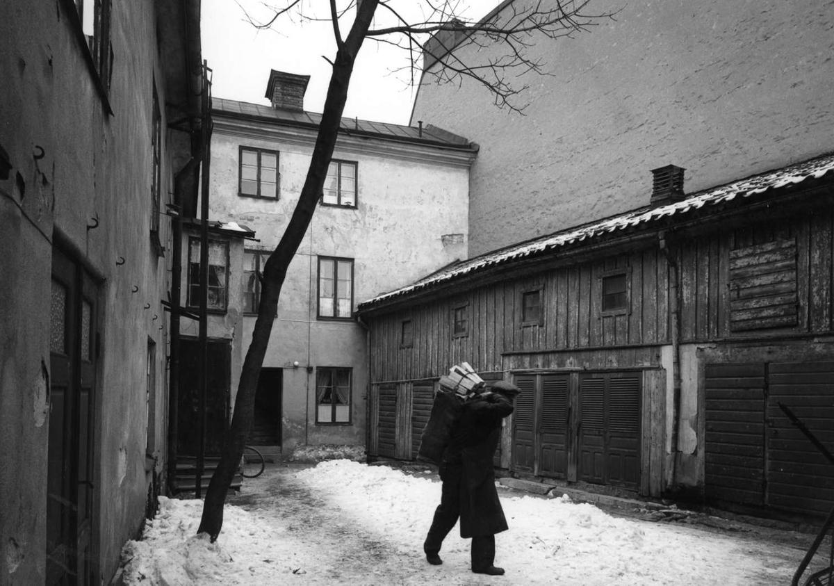 Man bär ved på innergård i kvarteret S:t Per, Uppsala, mitten av 1960-talet