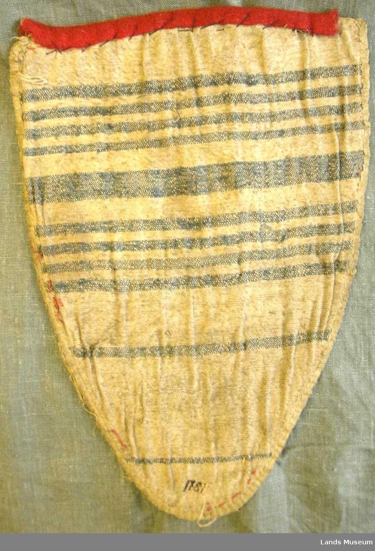 Brystduk av rødt ullstoff med påbroderte hvite, avlange glassperler og beige tråd. Trekantformet og avrundet nederst, gult kant omkring. På baksiden hvitt linstoff med blå striper og påskrevet årstall 1781. Opprinnelig bryststykket av kvinnedrakt.