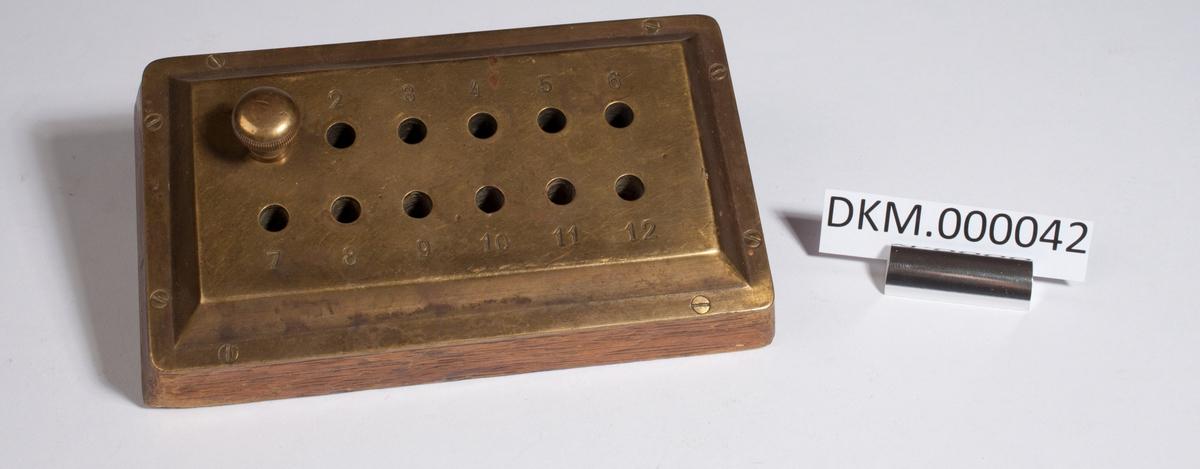 Rektangulære, lav trekloss med en messingplate skrudd fast på toppen. Det er boret 12 hull i hver teller som er nummererte fra 1 til 12, tallene er stemplet i messingplata.