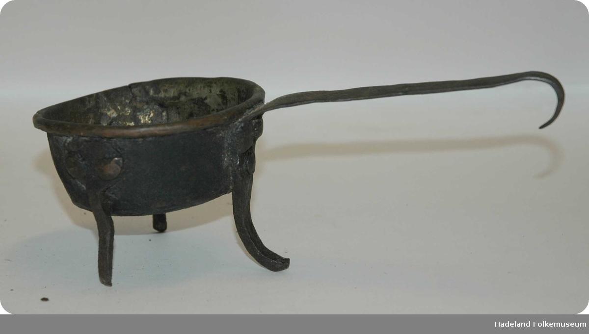Rund kobberpotte med med skaft og tre bein. Beina er  av jern og er naglet fast. Handtaket og det ene beinet er laget av et stykke. Håndtaket er bøyd som en krok i enden. En liten sprekk i selve kjelen.