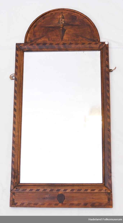 Speil i mørk treramme. Ilagte dekorelementer i ramme. Skade i dekorstjerne i rammens topp.