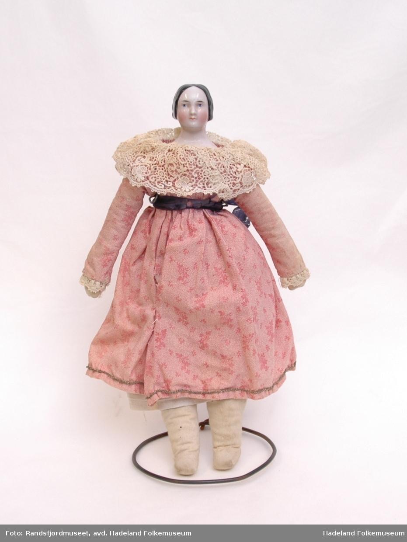 Hode av porselen, kropp av stoff. Kjole av bomullslerret med bred blondekrage og blondekant nederst på kjolen. Silkeband rundt livet. Jernstativ til å holde dukken oppe.