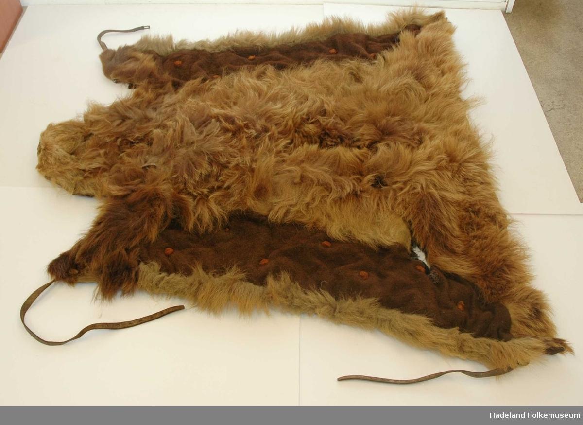 Helt bjørneskinn med utfyllende kanter i stoff på langsidene. Samme stoffet er sydd på baksiden. Stoffet er innvevd med korte dyrehår. Lærreimer til å spenne fast med.  Foret