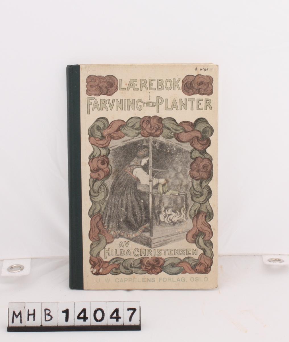 Rektangulær bok med pappinnbinding og grønn rygg. På forsiden er en kvinne i bunad som plantefarger i jerngryte over åpen ild. Motivet er innrammet av røde og grønne ullhespler.