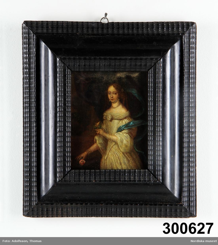 """Katalogkort: """"Tavla, porträtt, olja på koppar, 1600-tal [med blyerts], Hendrik Münnichofen tillskriven. Osign. Kristina? [med blyerts]. Ung dam, knästycke, stående åt vänster. I håret ett smycke, som håller fast en ljusblå slöja, pärlörhängen och pärlhalsband. Vit urringad klänning, pärlband i flera varv runt handlederna. Vänster hand upplyft, hållande en liten blombukett, den högra fattar en ros på ett bord med mörkviolett duk. Skriven text på baksidan [med blyerts]. kraftig svartmålad profilerad ram, med hopplist. Inköpt av Vera och Naja Cedergren på Bukowski dec 1935 nr 29 och i katalogen med frågetecken tillskriven Münnichhofen. Ur Chr. Eichhorns samling. Inbränt i ramen: V o NC (=Vera och Naja Cedergren). Blyertscirkel (?) nedanför hakan. Hela ytan täckt av små fina bruna prickar. Sprickor i ramens fogar. Bilaga. SE 1977 [=Sigrid Eklund]. test. gåva av fröken Naja Cedergren, Nybrogatan 27, Stockholm 1976-10-19."""""""