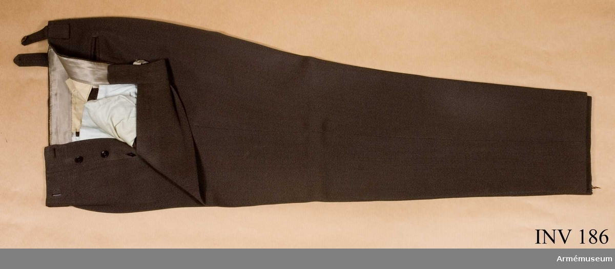 Stl B 154. Byxan är mörk greå-brun-grön med 4 st fickor, 2 st  snedskurna fram och 2 raksurna bak. Gylfen knäpps med 5 st  knappar. På insidan 4 st knappar avsedda för hängslen. Två hängselstroppar med knappar baktill.