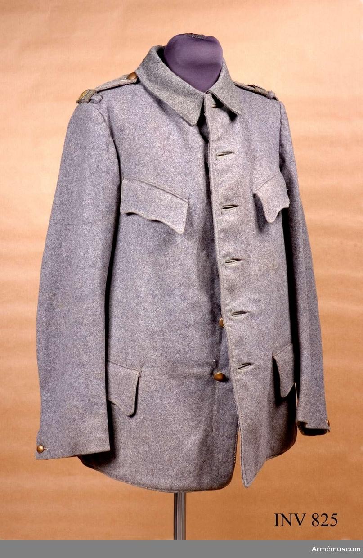 """Stl B 50. S k ersättningsmodell. Användes av dåvarande  landstormen och senare lokalförsvarsförband. Till denna uniform  användes mössa m/1923 eller första typen av """"båtmössa"""" =  fältmössa. Sydda av grått kommisskläde. Enkelradig med sex bronsfärgade knappar, något kupade och märkta """"Sporrong"""". Insticksfickor med fasonerade lock på bröstet och sidorna. Små sprund nedtill i sidsömmarna. Även nedtill på ärmarna, vilka knäpps med liten, något kupad och räfflad knapp. Ytterligare en knapp om man vill göra ärmen trängre. Axelklaffar fastsydda vid ärmsömmen och  knapp vid kragen. Axelhylsa av grå metall med """"L 19"""" målat gult.  Hälla på axeln. Foder av grått bomullstyg, något ljusare i  ärmarna. Stor innerficka vid vänster bröst och liten ficka på  höger, nedre sidostycke, för första förband. Två stora hankar av  fodertyget vid fodersidans bakre ärmsöm, för upphängning. Fodret  märkt med svart """"I 19"""" under kunglig krona 1917 ID."""