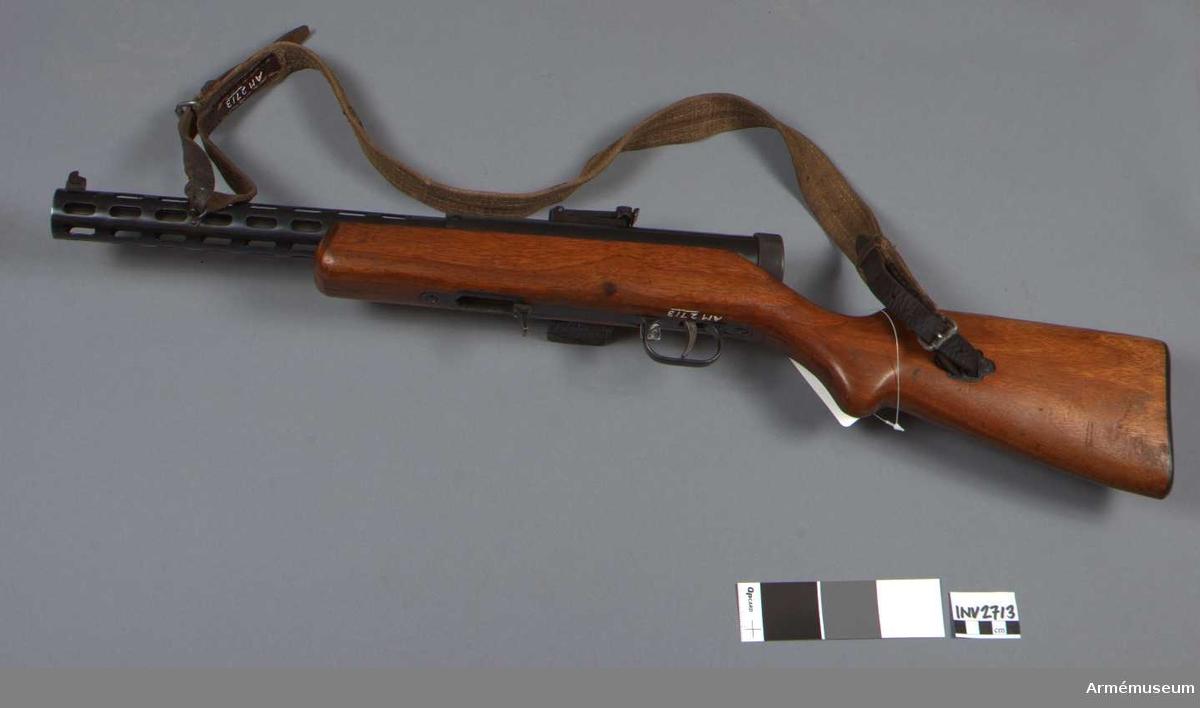Består av: 1 kulsprutepistol, 1 gevärsrem av väv (originaltillv.), 1 läskstång. Vapnet märkt med (SA) Suomen Armeija.