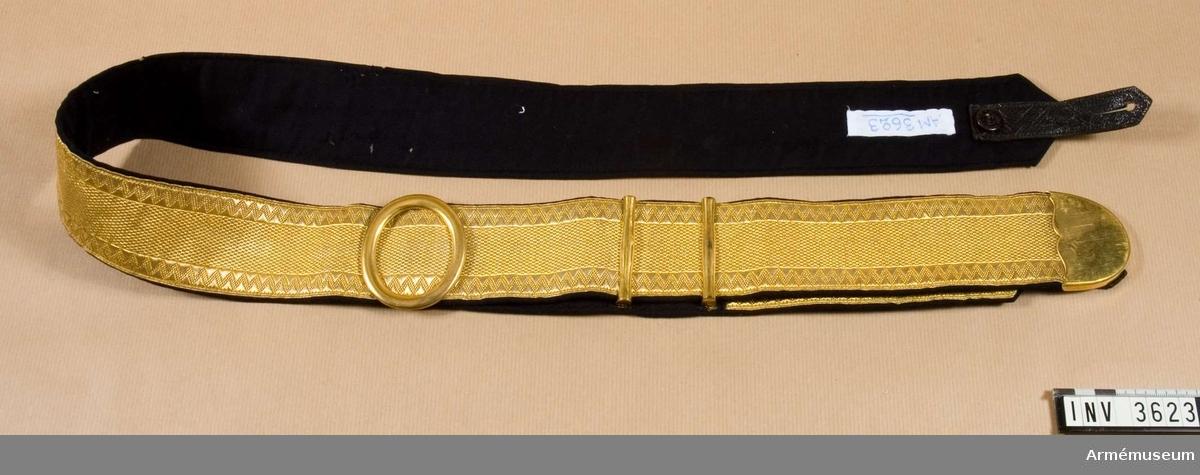 Rem m/1881 till kartuschlåda m/1893 för Andra Göta artilleriregemente A 6. Kartuschrem av guldgalon, artilleriets modell, med förgyllda beslag. Fodrad med mörkblått kläde. I  ändarna dubbel rem av läder med knapphål och knapp märkt MEA, för fastsättning i ringen på kartuschlådan. Remmen är reglerbar  på avigsidan under den ovala ringen, spännet.