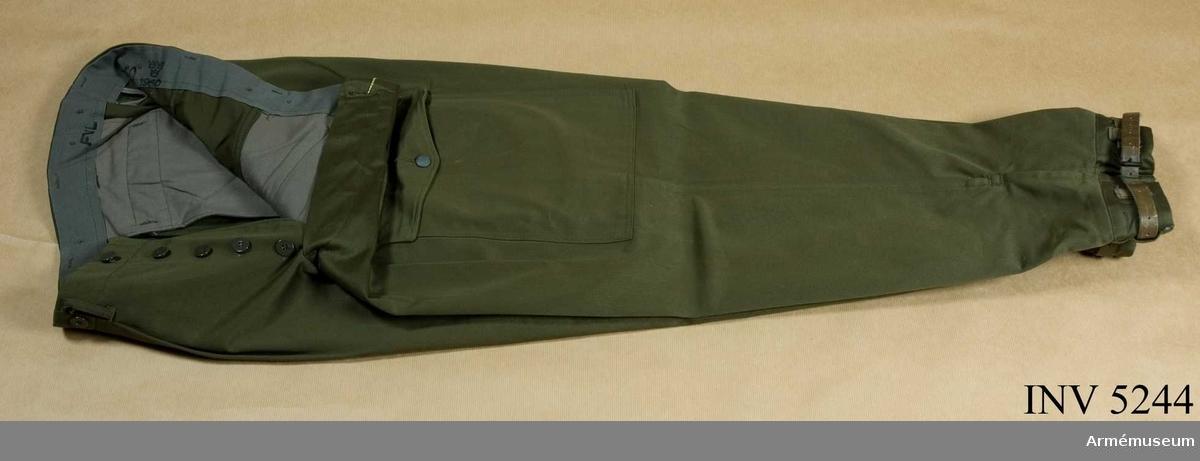 Skick som nya.Storlek: C 50. Tillverkade av olivgrönt bomullstyg i satinbindning. Har fasta damasker och två framfickor, två  benfickor, en bakficka och hällor för bälte. De är märkta i  linningen.  Samhörande nr: AM.005242 - AM.005244.