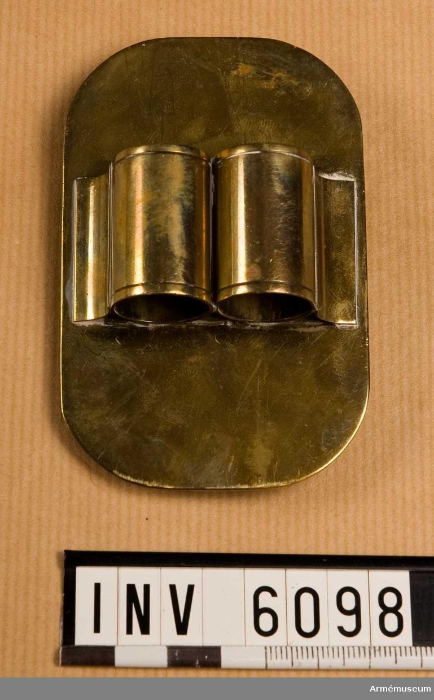Av mässing med oval botten. På baksidan öglor avsedda att fästa i hål i trumremmen. På plåtens framsida, mitt på och tvärs över denna finns två runda hållare för trumpinnar; invändigt klädda m grön filt.  Samhörande nr är 5828-5899, 6000-6099, 6200-6212