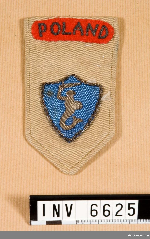 Längd: 120 mm. Bredd: 65 mm. Att sätta över axelklaffen. På rött ylletyg är POLAND broderat  med silversnodd. Emblem i silver på blå sköld. Warszawas  vapenbild.