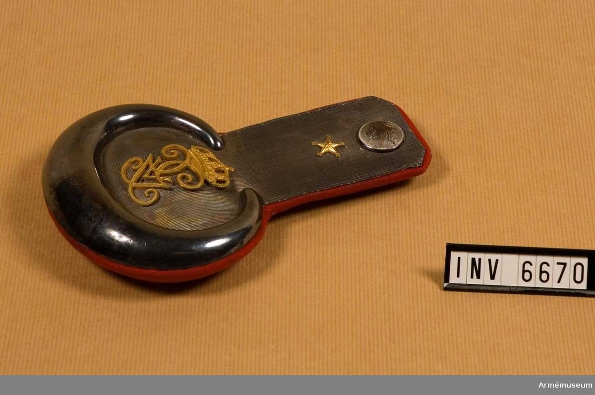 Gott skick. Mått: 190 mm mittlängd, 130 mm högsta bredd. Matta av galon i silver och nedre delens plåt av försilvrad metall. Konung Gustav V:s namnchiffer m/1908, mattförgyllt, 60 mm högt. Som gradbeteckning en förgylld stjärna placerad  strax under regementets knapp i silver. Foder i rött kläde och  en epåletthake i silver märkt GA & AD EM.