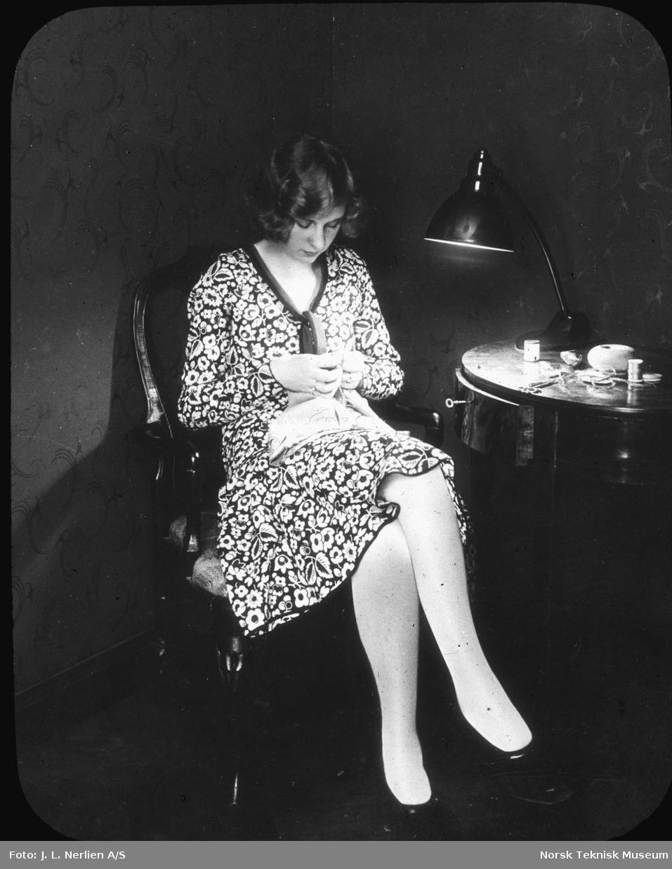 Kvinne sitter og syr under elektrisk lampe, 1930-tallet