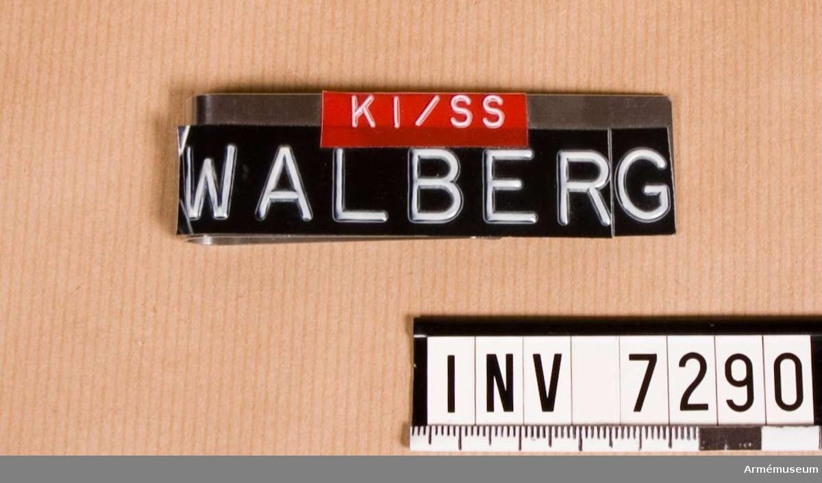 Text: Erik Walberg K1/SS. Utförd i aluminium med klämma. På framsidan påsatt en remsa av svart tape med vit präglad text: Walberg. Över namnet sitter en röd tape med texten: K1/SS.  På frånsidan tre kronorsstämpel. Gott skick 211. Gåva av Erik Walberg anställd på Armémuseum, Vapenavdelningen. Han har använt detta märke vid värnpliktstjänstgöring. Namnskylt bärs enligt regementschefs bestämmande av värnpliktiga under grundutbildning och av befäl i trupptjänst under tjänstgöringstid. Anbringas på vänstra ficklocket på vapenrock m/1960, jacka m/1968, skjorta m/1960 och m/1968 samt förses med uppgift om innehavarens namn, grad (tjänst eller födelsenummer), myndighet (förband) och erforderlig markering av underavdelning.  Märke för skyddombud eller skyddsassistent anbringas på högra delen av namnskylten. UNIA 1977 3:42 Namnskylt.  Samhörande gåva är AM.7290 - 7292