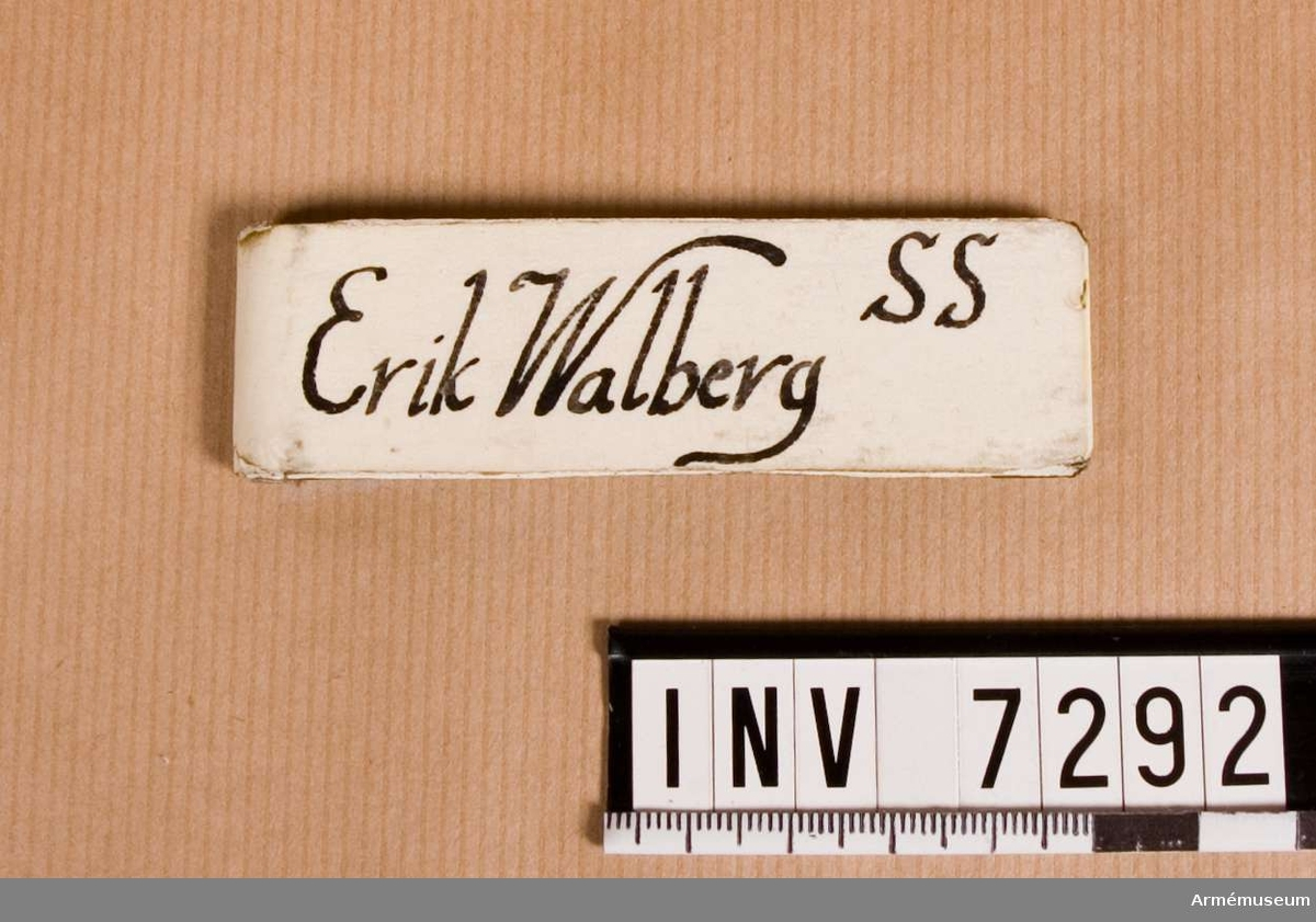 Utförd i aluminium med klämma. På framsidan påsatt en remsa av vit tape. Påskrivet med svart spritpenna: Erik Walberg. Uppe till höger: SS.