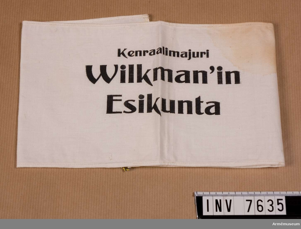"Armbindel, ""Wilkman'in Esikunta"". Finland. Text: ""Kenraalimajuri Wilkman'in Esikunta"" det vill säga Generalmajor Wilkmans stab. Vit armbindel med svart tryck.Mått 450 x 125 mm, färg vit A."