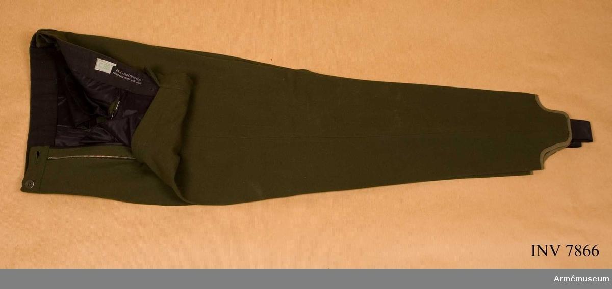 Storlek C 96. Färg olivgrön. Benvidd nedtill 350 mm. Benvidd 660 mm. Midja (byxlivvidd) 840 mm.Tillverkade av olivgrönt tyg, avsmalnade nedtill och försedda med hålfotshällor av resår, har två sidfickor och två bakfickor samt hällor för bälte. Märkta i linningen C 96, ull-polyester pressas med våt duk.
