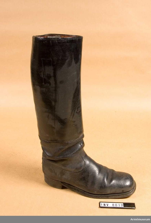 Skaftet i lackerat läder är påsytt foten ovanför ankeln. I  foten är lädret grovt narvat, sulan är randsydd med  förstärkning. Stöveln är fodrad med läder. Skaftets höjd + skohöjd 450 mm.