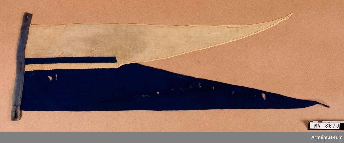 Vimpel. Längd 670 mm. Höjd 210 mm. Vikt 22,3 g ca. Hälften blå och hälften gul. Maskinsydda sömmar. Dubbelt ylleband på kortsidan för fastsättning vid lansen. Bandet är försett med tre knapphål. Fastmonteras med det blå fältet uppåt.