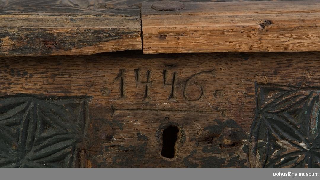 """Rektangulär med välvt lock. Locket har ett smitt handtag mittpå. Järnskoningar runt alla hörn samt järnband som löper tvärsöver locket och går över i gångjärn baktill. Ytan är täckt av rosetter i olika storlek, utförda i karvsnitt. Målad sekundärt med grön och svart färg. Röd färg skymtar undertill. På framsidan är """"1446"""" inskuret. Nyckelskylt och nyckel saknas. Talet """"1446"""" troligen ej årtal. Mycket sliten. Rostskyddsbehandlad. Skadedjursangrepp.  Litt.; Anker, Peter, Kister og skrin, C. Huitfeldts förlag, Oslo, 1989.  Ur handskrivna katalogen 1957-1958: Skrin, järnbeslaget, snidat L. 56; Br. 44; H. 29 cm; karvsnitt, grönmålat; handtag på locket. En del av locket är löst. b), Mått: 56,5 x 17,5 cm en bit härav är nytillsatt.  Nyckeln c) L.7,8 cm framtill på skrinet. """"1446"""". Trasigt; mask, rost."""