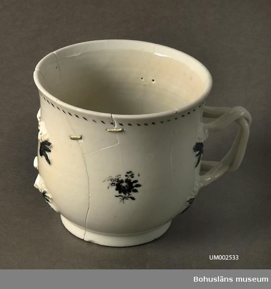 Tillverkad i Kina. Runt kärl med utåtbuktande sidor; vitt med små målade svart blommor. I ena sidan är det en hänkel med fyra fästpunkter. Vid fästpunkterna är det blommor i relief. En hänkel saknas. Sprickor och lagningar.  Ur handskrivna katalogen 1957-1958: Mugg 1700-t. H.: c:a 9,7 cm Mynningsdiamet: 10,4 cm. Vitt porslin m. små blommor i svart. Ett öra i ena sidan, flätat. Örat på motsatta sidan är bortslaget. Muggen är spräckt och lagad på flera ställen.  lappkatalog: 62