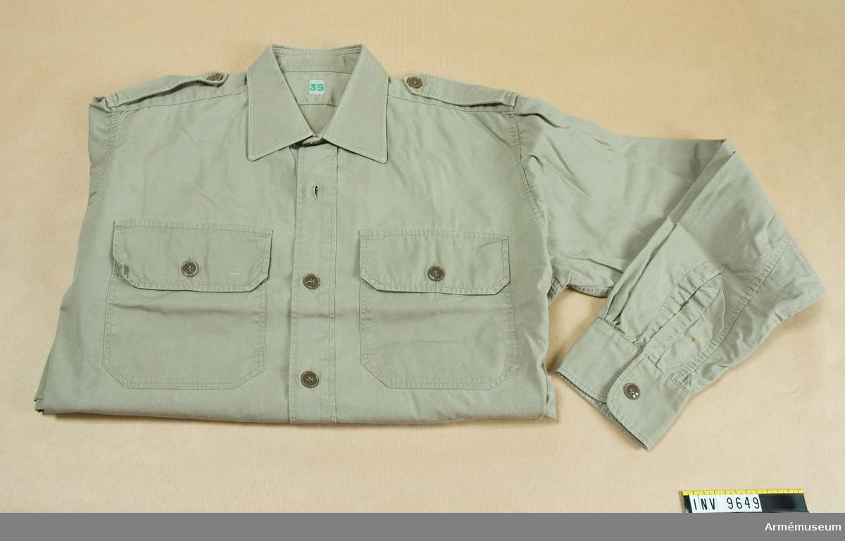 Skjorta m/1961.Tillverkad i khakifärgat bomullstyg s k poplin. Har nedvikt mjuk krage, fasta axelklaffar, två utanpåstickade bröstfickor med knäppbara ficklock samt långa ärmar med knäppbar  ärmlinning.