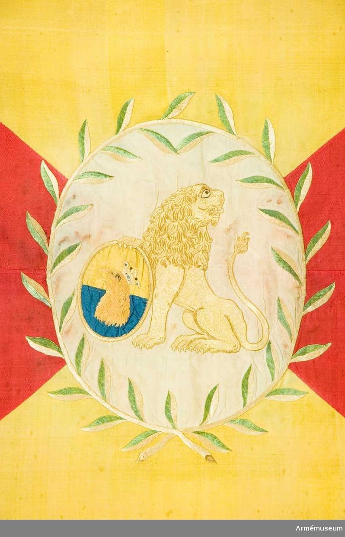Grupp B I  Duk av sidenkypert, fyrstyckad, gul och röd, i mitten broderat en sköld med Skånes vapen, lika å båda sidor, ett av en enkel lagerkrans i olika gröna silken begränsat, ovalt, vitt fält av påsytt siden varå ett sittande, åt höger vänt, bakåtseende lejon i gult silke, med ena tassen stödjande en liten gulkantad delad gul och blå sköld vari ett rött, krönt griphuvud, kantad med sidenband, gult å det gula, rött å det röda, fäst med rött sidenband och ovala, förgyllda spikar.