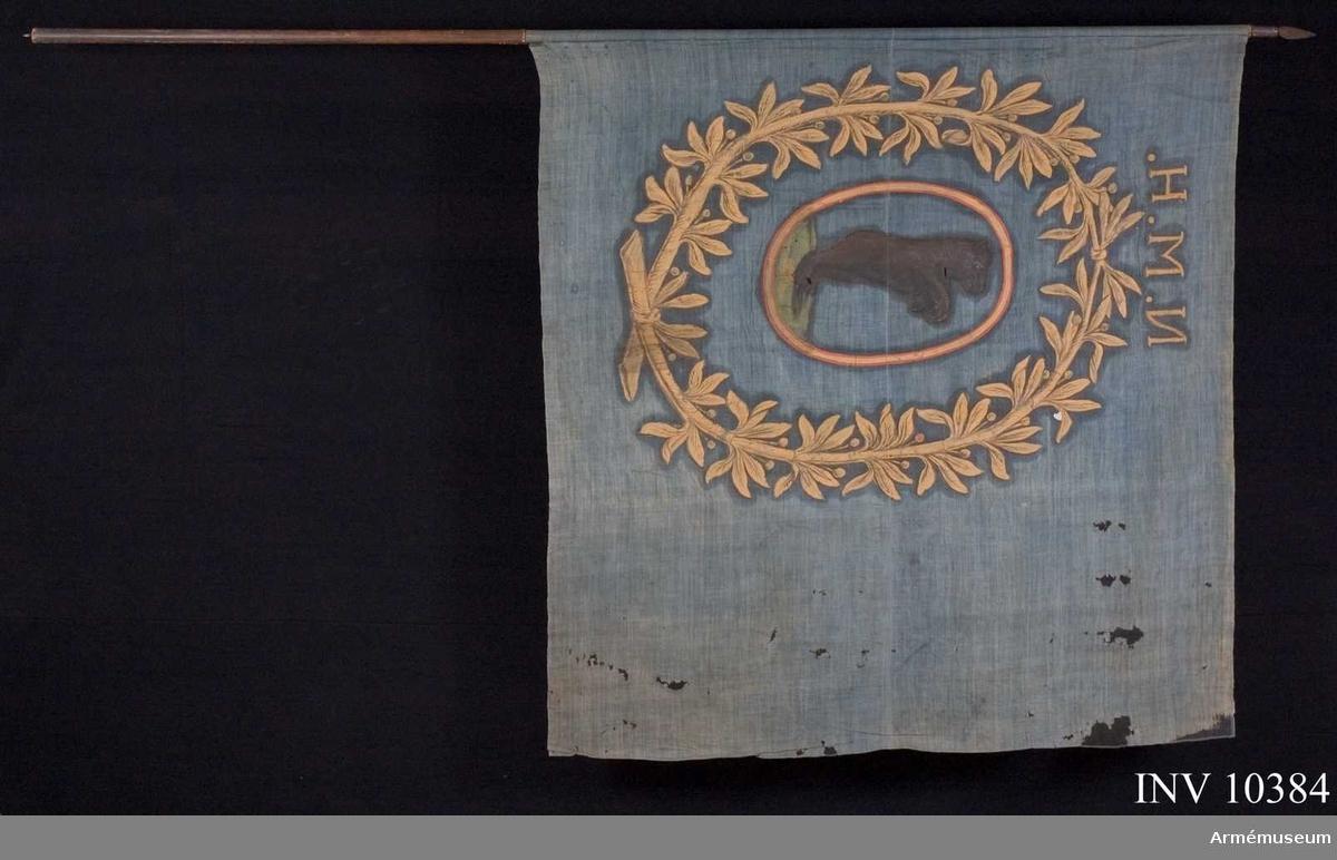 Grupp B I.  Fanduk av blått lärft med målade emblem lika på båda sidor: en oval, gul och rödkantad sköld, vari står en björn, brun och svartmålad, vänd från stången, stående på grön mark; allt  omgivet av lagerkrans, oval, av två upptill och nedtill hopknutna lagerkvistar med blad och bär, allt i gult. Ovan lagerkransen: N.M.H. Fäst med läderremmar och järnspik. Stång av furu, brunsvartmålad. Spets av järn, holk och blad i ett stycke. Bladet lancettformigt.
