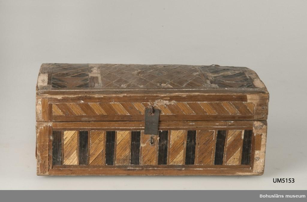 """Rektangulär låda med något välvt lock. Tappad konstruktion. Utsidan är klädd med halmmosaik i geometriskt mönster. Halmen är infärgad i olika nyanser. Fastspikade gångjärn av läder, kan ha ersatt äldre av samma typ. Metall lås med bygel och defekt ovandel. Halmmosaiken saknas på ett flertal ställen.  Litteratur: Årsboken Kulturen 1937, Tedosa med applikationsdekor av halm, s. 56-57, samt Blekingeboken årg 73 1995, årsbok för Blekinge läns Hembygdsförbund och Blekinge Läns Museum, """"Med färgad halm inlagt och med figurer utzirat arbete"""" - halmintarsia i 1700-talets Ronneby, s. 57-78.  Ur handskrivna katalogen 1957-1958: Litet träskrin m. halmstråinlägg L. 18, Br 10, H. 7,5 cm; gångjärn av läder; låsn. medelst ett överfall (trasigt) och en bygel. Inläggn. trasig. S. Hellevigsgat. 11  Lappkatalog: 84"""