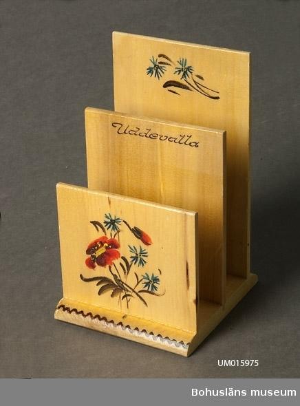"""Bottenplatta med tre uppstående plattor med målad blomdekor och namnet """"Uddevalla"""".  Se UM015810"""