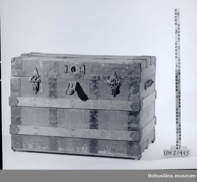 Kofferten består av stomme av trä, klädd med väv så väl in-som utvändigt. Den är förstärkt med träribbor, samt plåtskodd. Läderhandtag på sidorna. Två spännlås av järn ur funktion. Låsanordning av mässing. Invändigt extra insats för packning.  UMFF 21:8