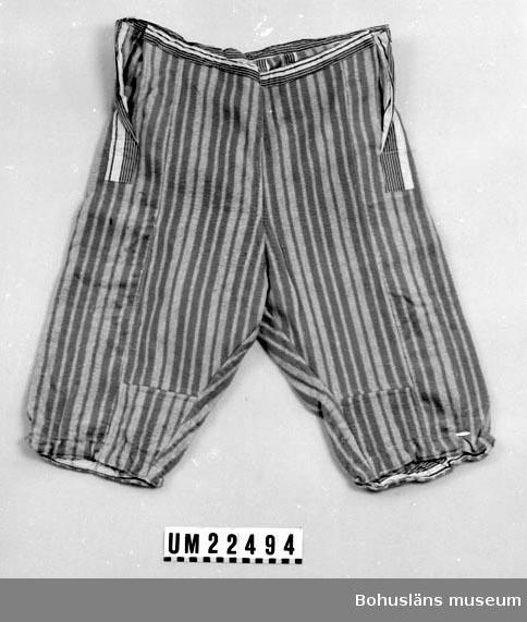 410 Mått/Vikt ! BL 36, BV 23 CM 594 Landskap BOHUSLÄN  Blågrå randiga benkläder med brunvitrandig bård runt midjan och i sprunden i sidorna.  UMFF 113:12
