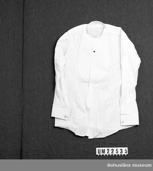 """410 Mått/Vikt ! ÄL 61 CM 594 Landskap BOHUSLÄN  Storlek 39. Vit frackskjorta med stärkbröst. Kragknapp och nackknapp. En svart knapp framtill, två ovala manschettknappar i gulmetall med rund pärlemoknapp i mitten,  märkt: """"SD"""".  Sammanhör med UM22534.  UMFF 125:10"""
